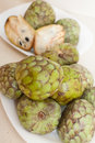 Cherimoya on saucers on kitchen table Royalty Free Stock Photo