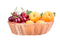 Cherries and apricots in wooden box on white background Royalty Free Stock Photo