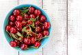 Cherries in a blue bowl on a white wooden background ripe with leaves Stock Images