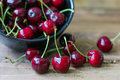 Cherries in bowl on wooden table Royalty Free Stock Photo