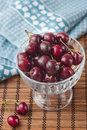 Cherries in glass bowl blue napkin Royalty Free Stock Photo