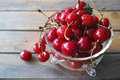 Cherries in a glass bowl fresh red against wooden background Stock Photos