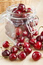 Cherries in glass jar on kitchen table Stock Image