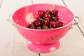 Cherries in pink colander on wooden underground Royalty Free Stock Image