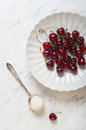 Cherries on a plate on a marble table white Stock Images