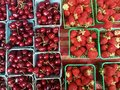 Cherries and strawberries in baskets for sale at farmer's market Royalty Free Stock Photo