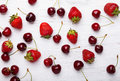 Cherries and strawberries on the  white wooden table, top view Royalty Free Stock Photo