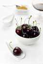 Cherries white spoon and bowl, sherry glass, sugar Royalty Free Stock Images