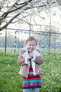 Cherry blossoms fall and a girl is verry happy cute adorable nice little smiling sitting under or apple tree Royalty Free Stock Photo