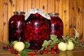 Cherry canned many cherries in three large banks on wood background Royalty Free Stock Photography