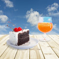 Cherry chocolate cake and orange juice setting on wood table blue sky blurry background soft focus Stock Images