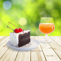 Cherry chocolate cake and orange juice setting on wood table green blurry background soft focus Stock Image