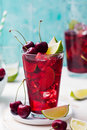 Cherry cola, limeade, lemonade, cocktail in a tall glass on a white, turquoise background Royalty Free Stock Photo