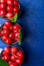 Cherry in enamel cup on blue wooden background. Healthy, summer fruit. Cherries. Top view. Copy space. Royalty Free Stock Photo
