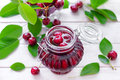 Cherry jam in a glass jar and fresh fruits with leaves Royalty Free Stock Images