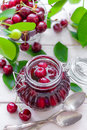 Cherry jam in a glass jar and fresh fruits with leaves Royalty Free Stock Photos