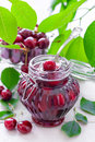 Cherry jam in a glass jar and fresh fruits with leaves Stock Image