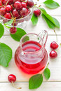 Cherry juice and fresh fruits with leaves Stock Image