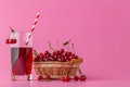 Cherry juice in a glass and pitcher on pink with ripe berries in Royalty Free Stock Photo