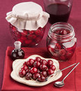 Cherry in juice in the pot on a red napkin Royalty Free Stock Photography