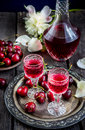 Cherry liquor in glasses, cherry and vintage bottle on metal tray. Royalty Free Stock Photo