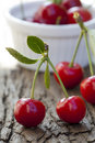 A cherry pair on stem in front of white bowl with other cherries Stock Images