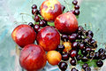 Cherry and peach on a wet glass table close up outdoor Stock Photography