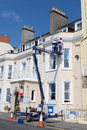 Cherry picking painting a picker being used by two men to paint the front of the atlantic hotel in tenby south wales united Stock Photo