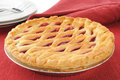 Cherry pie with a golden lattice crust and plates Royalty Free Stock Photos