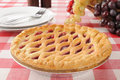 Cherry pie with a lattice crust on a picnic table Royalty Free Stock Photos