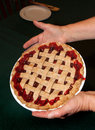 Cherry pie with lattice crust a whole golden flakey held in two hands Royalty Free Stock Image