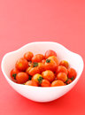 Cherry tomato in the bowl with pink background Royalty Free Stock Photography
