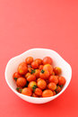 Cherry tomato in the bowl with pink background Stock Photos