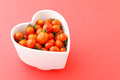 Cherry tomato in heart shape bowl with pink background Royalty Free Stock Photos