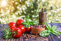 Cherry tomatoes basil pepper and pepper mill on wooden board Royalty Free Stock Images