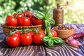 Cherry tomatoes basil pepper and pepper mill on wooden board Stock Photos