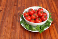 Cherry tomatoes in a bowl surrounded by green mache lettuce Stock Photography