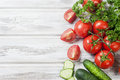 Cherry tomatoes on a branch, cucumber, parsley Royalty Free Stock Photo