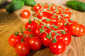 Cherry tomatoes on a branch near cucumbers and vegetables Stock Images