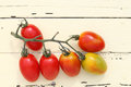 Cherry tomatoes branch of on wooden table Royalty Free Stock Image