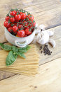 Cherry tomatoes garlic and spaghetti on a wooden table Stock Photo