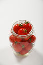 Cherry tomatoes in glass jar over white Royalty Free Stock Photo