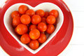 Cherry tomatoes in a heart shaped bowl on red plate close up of bright white wood background Stock Photo