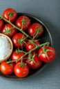 Cherry tomatoes with natural sea salt bunch of ripe red on the vine arranged on a plate a bowl of coarse for use as cooking Stock Images