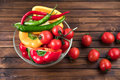 Cherry tomatoes and peppers in bowl on wooden table top texture