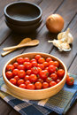 Cherry tomatoes in wooden bowl with garlic onion bowls and wooden spoons in the back photographed on wood with natural light Stock Photo