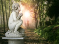 Cherub in a wood beautiful statue profile Stock Photos
