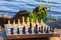 Chess board with chess pieces on rock with river embankment back Royalty Free Stock Photo