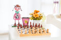 Chess with doll and flowers on table Stock Image