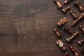 Chess figures on brown wooden table background Stock Photos